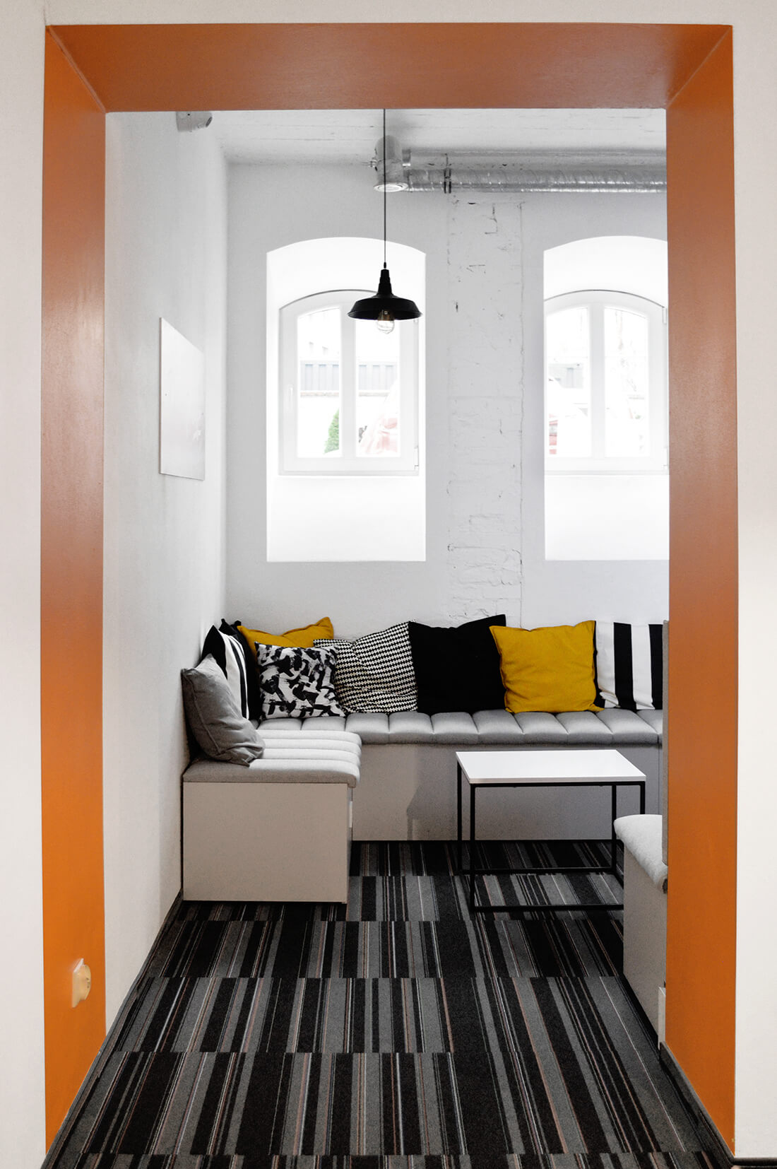 Projekt wnętrza jadalni, strefa z szarymi siedziskami z poduszkami