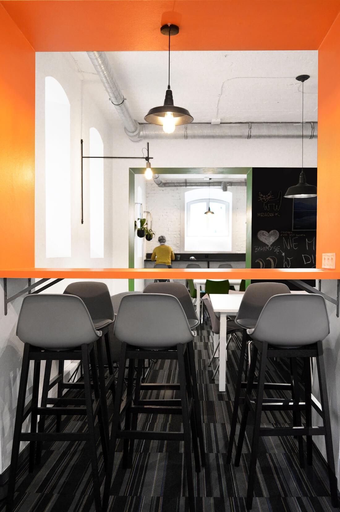 Projekt wnętrza jadalni we wrocławskiej firmie, pomarańczowa wnęka z blatem i hokerami